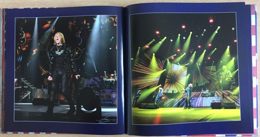 2 page spread from the book of photos in the Def Leppard London To Vegas box set. The left page shows singer Joe Elliot, dressed mainly in black, fists clenched by his side and mouth open wide as he sings powerfully. The right page shows a few of the entire band performing under a set of many green spotlights that are pointing in all directions to cover the stage.