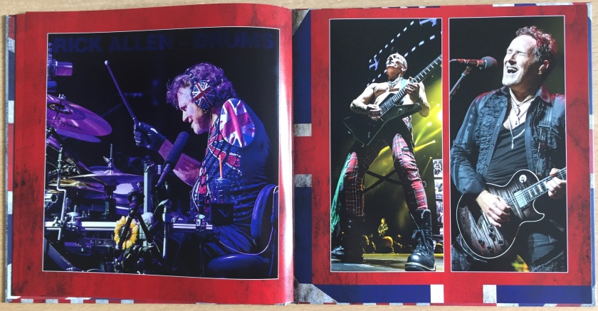 2 page spread from the book of photos in the Def Leppard London To Vegas box set. The left page shows one-armed drummer Rick Allen performing, wearing Union Jack emblazoned headphones, and a Union Jack patch over the unused arm hole of his jacket. The right hand page shows guitarists Vivian Campbell and Phil Collen performing, Vivian singing as he plays while Phil performs topless.