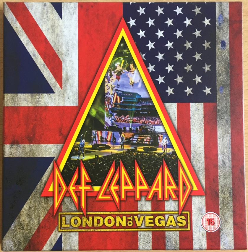 Front cover of the Def Leppard London To Vegas box set. The background is split into 2 vertical sections, containing half of the Union Jack and American flags respectively. A large triangle in the middle, with a double border of red and yellow, features a colourful photo of the band in concert, with singer Joe Elliot on a platform stretching out from the stage into the audience. Across the bottom of the triangle, large yellow text with a red border says Def Leppard, in a font made only of straight and diagonal lines. Below this, in a yellow box, yellow text says London To Vegas.