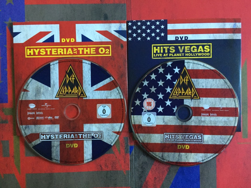 The DVD discs for Hysteria At The O2 and Hits Vegas Live At Planet Hollywood by Def Leppard. The background of each disc shows the central portion of the Union Jack or American flag respectively. The Def Leppard logo, made of a red and yellow bordered triangle with the yellow lettering of the band name filling the centre, sits in the top centre of the disc. The show name is in the bottom section of the disc, as yellow text inside a yellow bordered box.