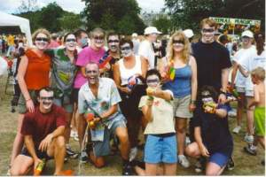 A smiling team of 10 people, including Glen, their faces painted in white, with black across the eyes, and all holding water pistols.