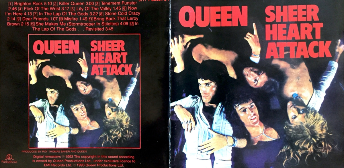 Booklet cover spread for the Queen album Queen 2. The back cover on the left has the tracks listed in red on a black background, above a smaller copy of the front cover. The front cover on the right shows the 4 band members laying on their backs and covered in water. Freddie and Brian are fully clothed and facing the right way up, while John and Roger appear upside down and have their shirts open to reveal their best chests. The colours are also over-exposed, giving it a more artistic feel. At the top, the words Queen Sheer Heart Attack, are in large red capital letters.