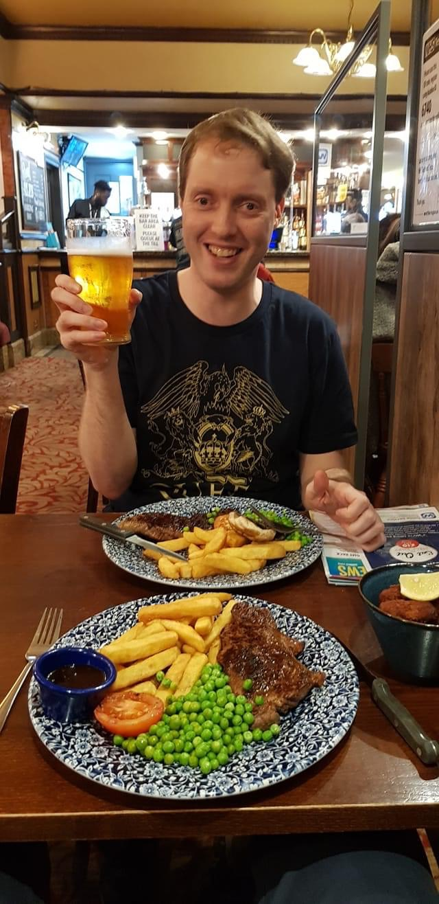 Glen sitting at a table in a pub, smiling as he holds up a pint of cider. In front of him is a dinner of streak and chips, with peas, mushroom and tomato.
