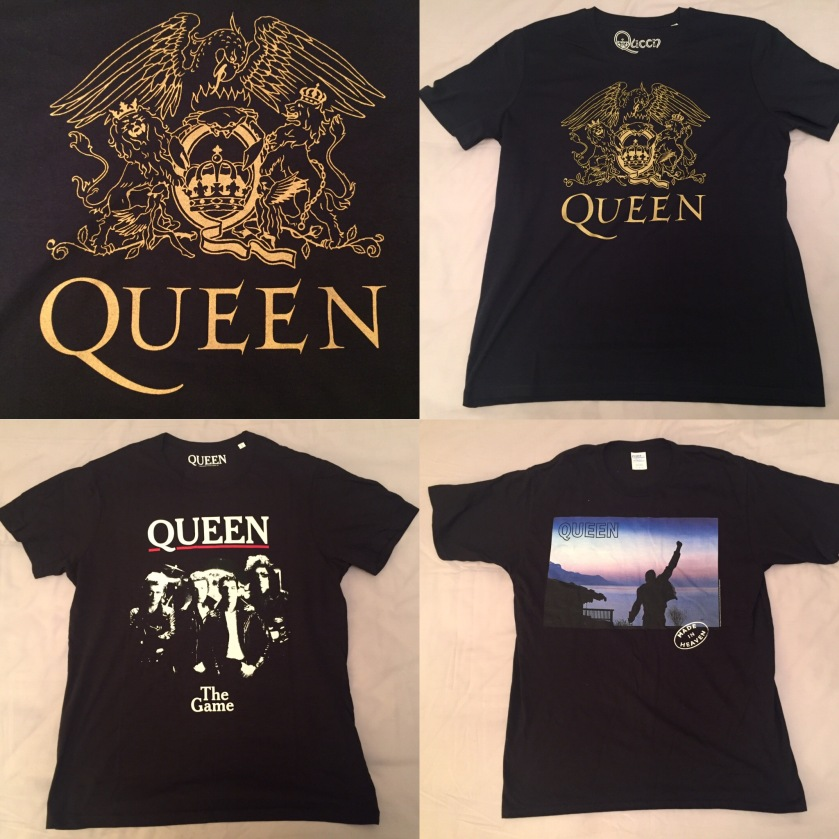 3 Queen t-shirts. One is dark blue with the Queen crest in large gold print, with the crest featuring a phoenix, lions and fairies. One is black, with a black and white image of the band posing together on the album cover for The Game. And one is black with a colour image of the Made In Heaven album cover, showing Freddie Mercury's statue looking out over a scenic sea view.