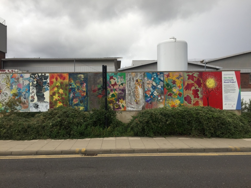 A long mural stretching along a wall by the road, made of several vertical panels, each containing a different piece of colourfully painted artwork. They all have a nature theme, with leaves, flowers, trees, birds, sunshine, etc. The final panel on the right shows that this is titled the Glen Road Community Mural Project.