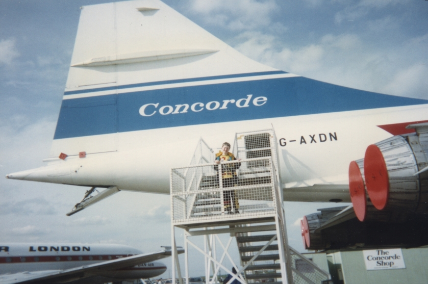 Glen in his childhood, standing on the steps leading up to Concorde, looking very small in comparison to the huge tail wing behind him.