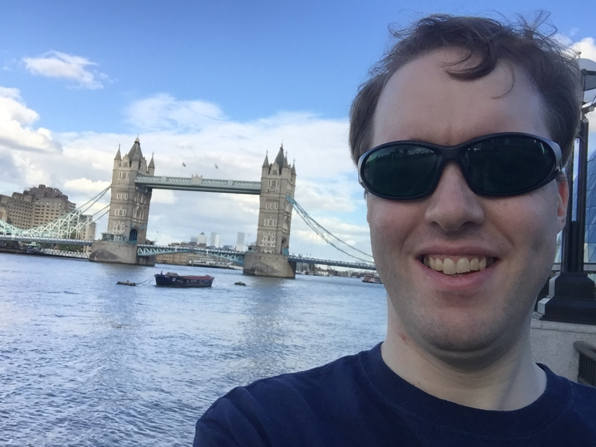 Selfie of Glen smiling and wearing dark glasses in front of Tower Bridge.
