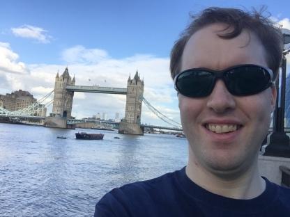 Selfie of Glen smiling and wearing dark glasses in front of Tower Bridge.
