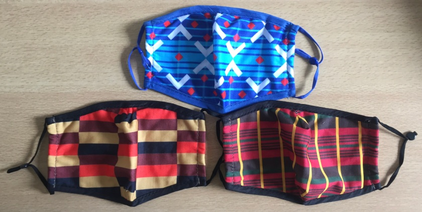 3 face masks, featuring colourful moquette designs from Routemaster buses, Victoria Line trains and District Line trains. They feature a variety of lines, stripes, blocks and diamond shapes to form their distinctive looks, with one mask predominantly blue and white, while the other 2 have a mixture of black, red, orange and yellow colours.