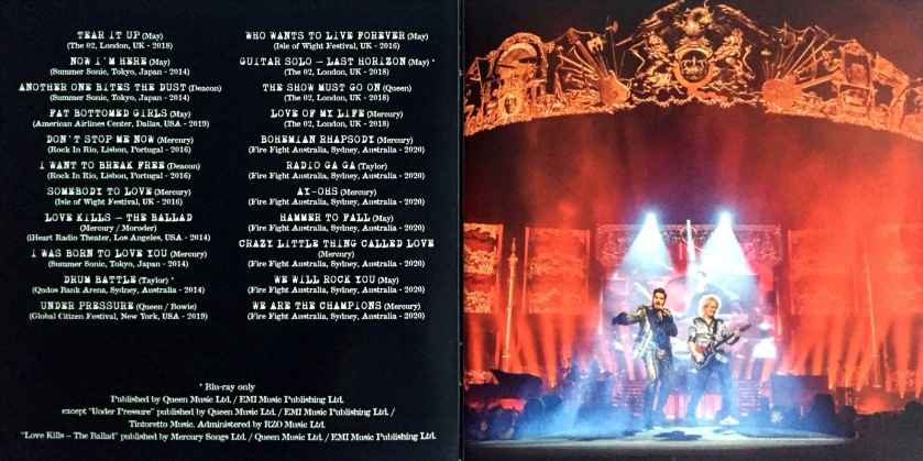 2-page spread from the Live Around The World album booklet by Queen and Adam Lambert. The left page shows the track listing, while the right page shows a photo of the band performing ons stage, spotlights shining down on all 3 members. High above them, a large and very ornate golden archway spans the stage, with the Queen crest in the centre.