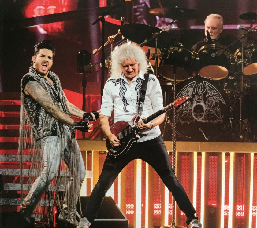 Brian May smiling and standing with legs wide apart as he plays the guitar. Adam Lambert, wearing a top with lots of chains hanging down to the floor and the short sleeves revealing his tattooed arms, is making a thrusting motion towards Brian, while shouting something towards the audience. Roger Taylor is on the drums in the background.