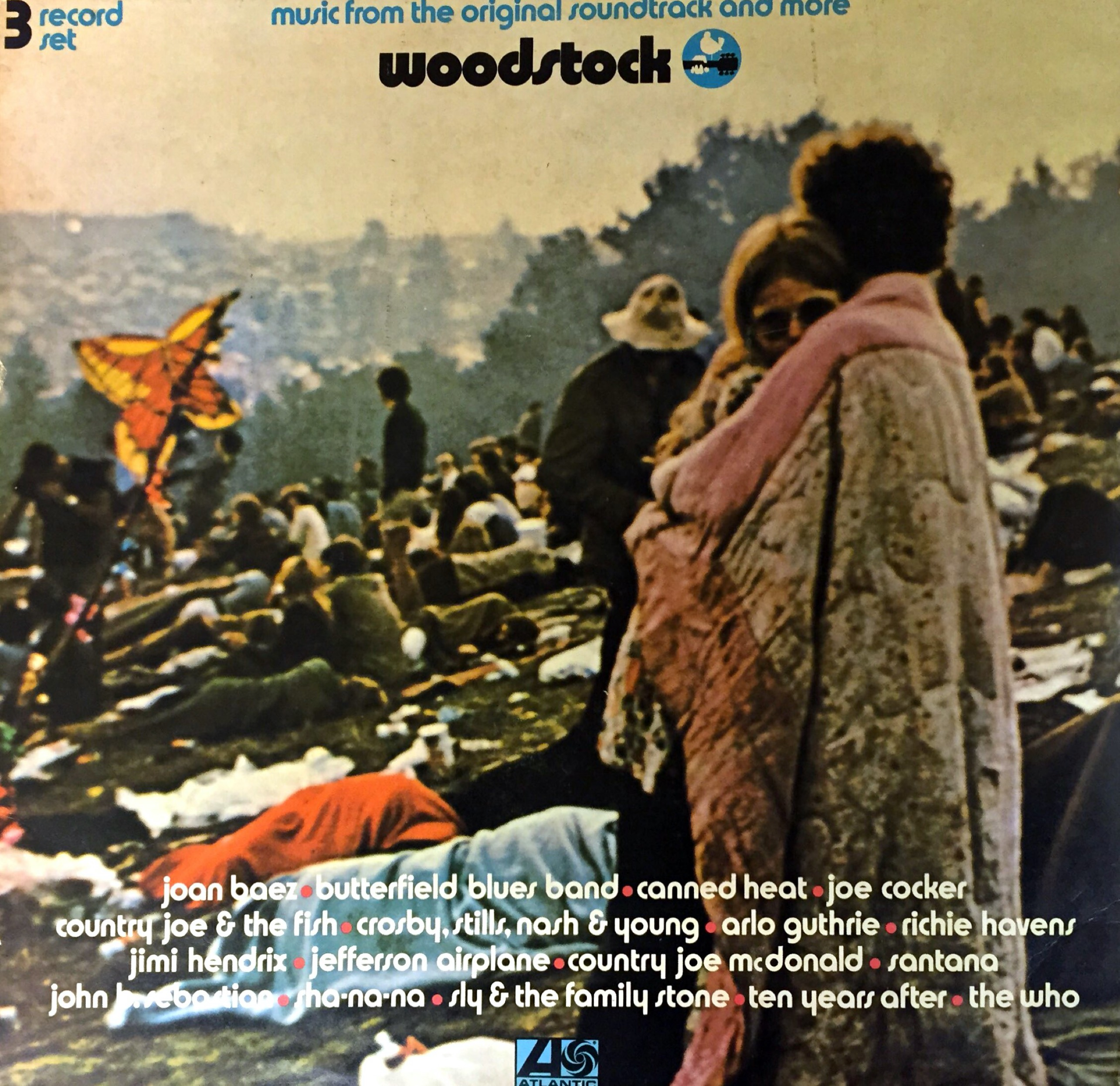 Woodstuck album cover, showing 2 people standing and embracing, while many others are laying down on the grass in the sunshine behind them.