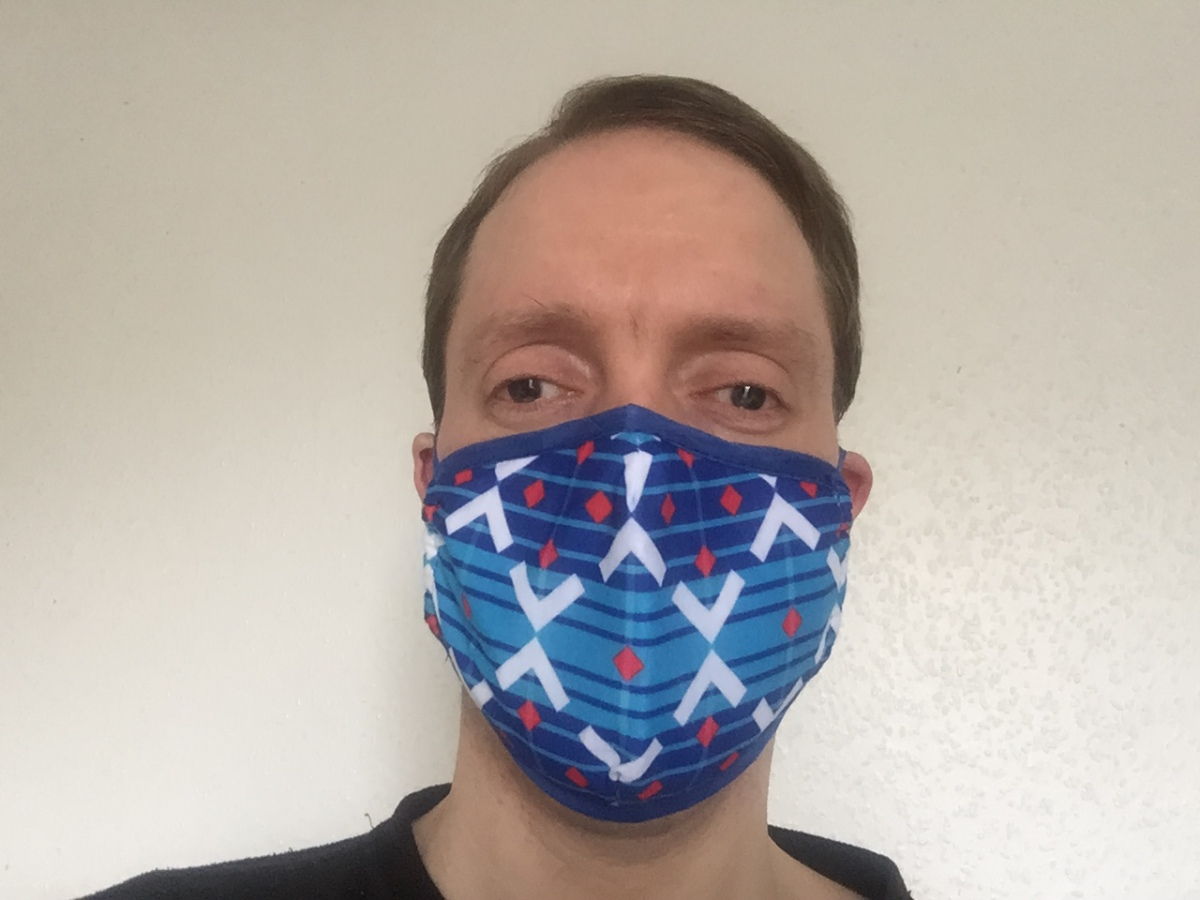 Selfie of Glen wearing a face mask decorated with a Victoria Line train moquette pattern. The pattern has alternating light blue and dark blue horizontal stripes of varying widths, overlaid with two zig-zagging white lines that form 3 diamond shapes, and there are small red diamonds spread around the pattern as well.