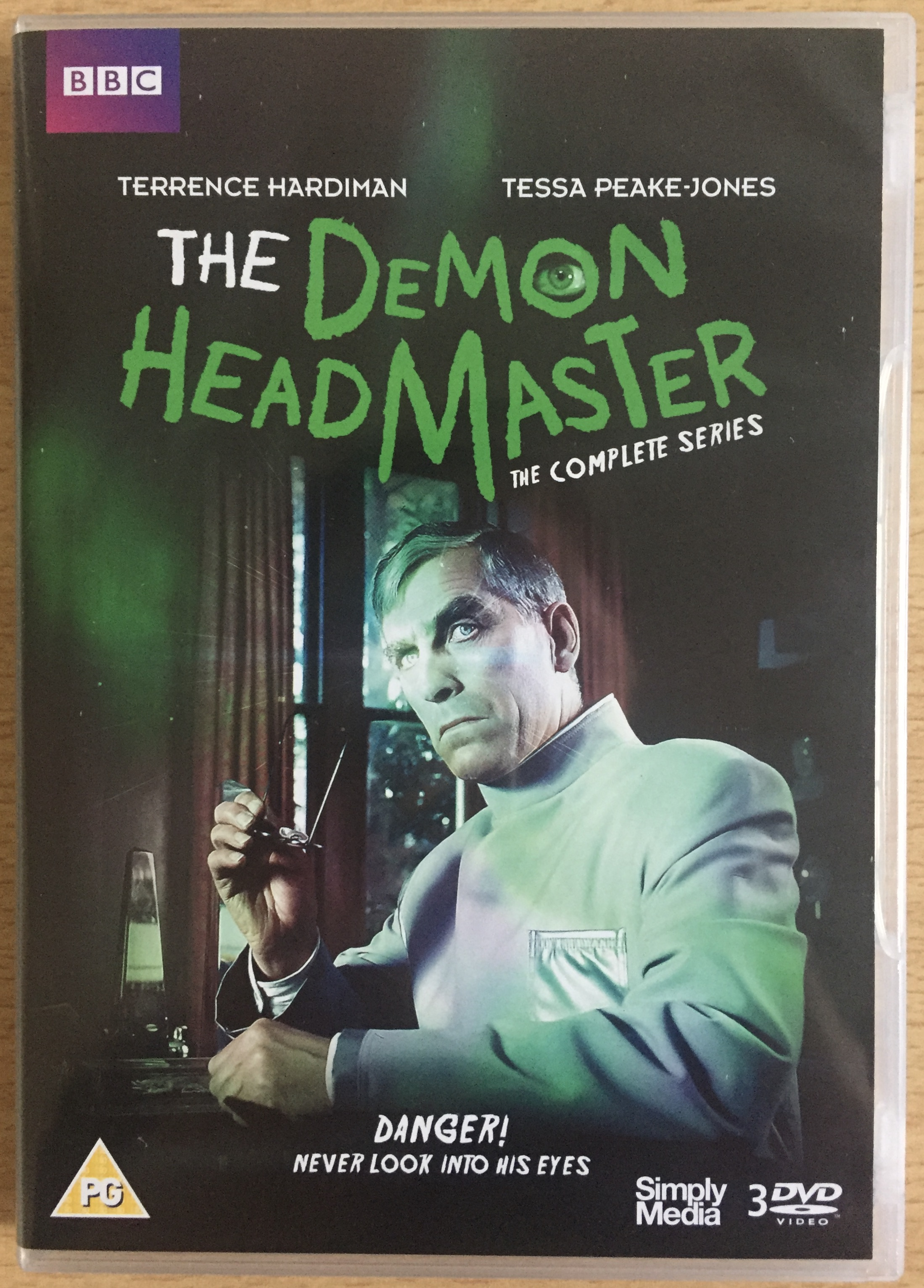 Front cover of the DVD for The Demon Headmaster, showing the title character with his glasses in his hand as he looks over to the side, seemingly at us.