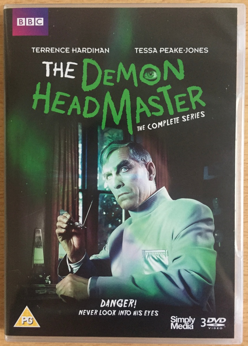 Front cover of the DVD for The Demon Headmaster, showing the title character with his glasses in his hand as he looks over to the side, seemingly at us. The strapline says Danger, do not look into his eyes. The DVD is rated PG.