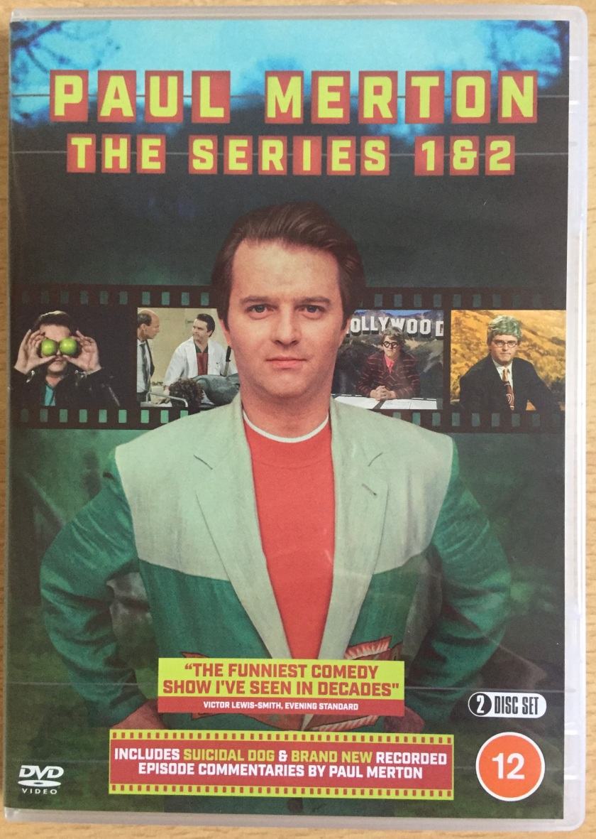 Front cover of the DVD for Paul Merton The Series, showing an image of him standing with his hands on his hips, with a film reel behind him showing images from the programme. The DVD is rated 12 and includes his short film Suicidal Dog and brand new audio commentaries by Paul.
