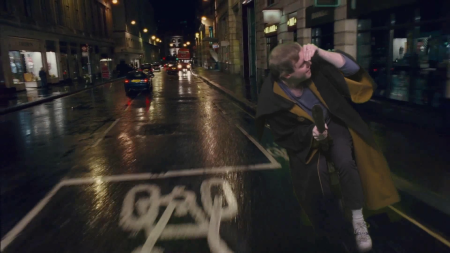 Glen looking around as he flies down a busy London street at night on a broomstick.