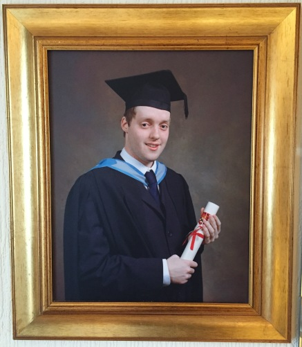 My graduation photo in a big gold frame. I'm wearing a dark navy suit and tie, with light blue strap around the neck, and a mortar board on my head. I'm smiling while holding a rolled up certificate tied with a red ribbon.