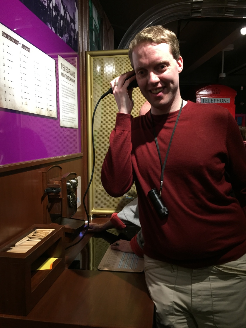 Glen smiling as he holds the receiver of a morse code device to his ear in a museum.
