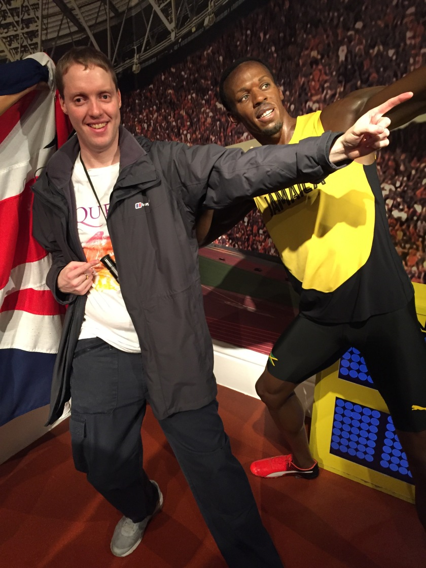 Glen next to Usain Bolt's waxwork at Madame Tussaud's, copying his lightning bolt pose where he leans on his back foot while pointing up and ahead with the opposite arm.