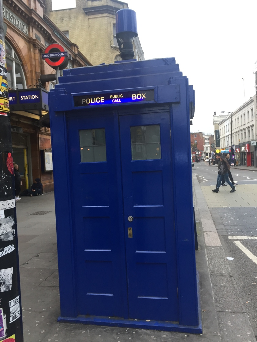Tall blue police call box, very similar to Doctor Who's Tardis, on the pavement outside Earl's Court Underground Station.