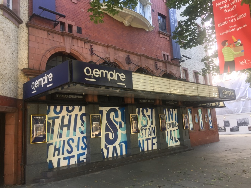 The front of the Shepherd's Bush Empire, now called the O2 Empire. White posters cover up the 4 windows along the front, with stylistic blue lettering that reads This Is Just An Interval, in reference to the shutdown enforced by the Covid pandemic.