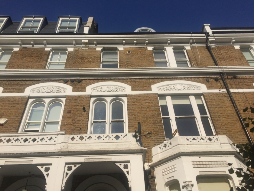 The upper 2 floors of 36 Sinclair Road, The white framed windows on the first floor have an ornately decorated arch above them, while the windows on the second floor don't have any special decoration.