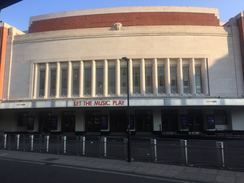 The Eventim Apollo, a large, wide building. Above the ground floor, which has steps leading up to multiple entrance doors, a narrow panel across the entire building features the venue's name and large red letters reading Let The Music Play. Above that, the building is mainly large white concrete, with a row of 14 tall, narrow windows stretching about halfway up. The very top of the venue has a red brick layer topped by a small layer of white concrete.