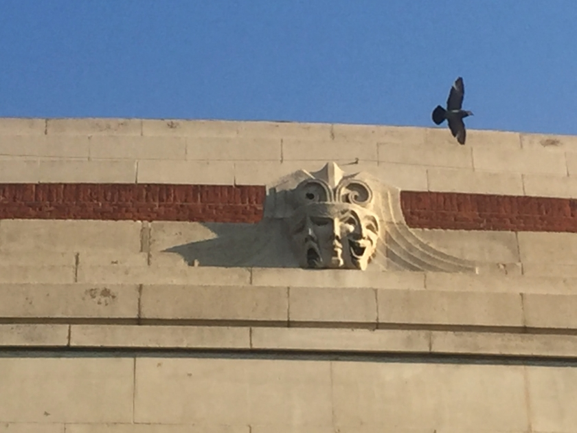 Close up of 3 theatrical faces sculpted into the concrete at the top of the Eventim Apollo, one with an exaggerated expression of sadness, one looking unemotional, and one looking very happy. A black coloured bird is flying past, its wings outstretched.
