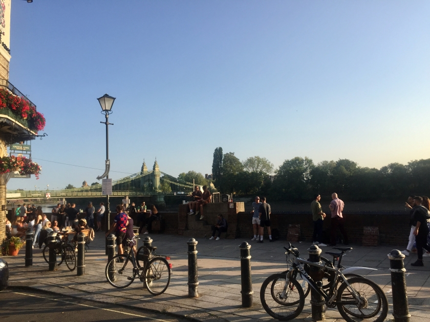 The riverside path next to the Rutland arms, busy with people either sitting at tables, or standing in pairs and small groups. A row of bollards, with bikes resting against some of them, separate the path from the cul-de-sac that leads up to it.