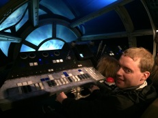 Glen sitting and grasping the steering control in the cockpit of the Millennium Falcon, the dashboard of which has black, white and blue chunky, tactile buttons that contrast well against the grey surface. Light outside the cockpit window gives the impression that he's zooming through space.
