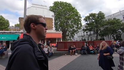 Glen wearing sunglasses as he walks down a busy street.