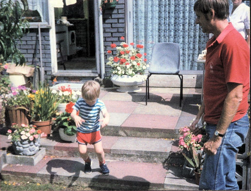 Glen as a child walking down a few paved steps from a patio into a garden, while his Dad watches.