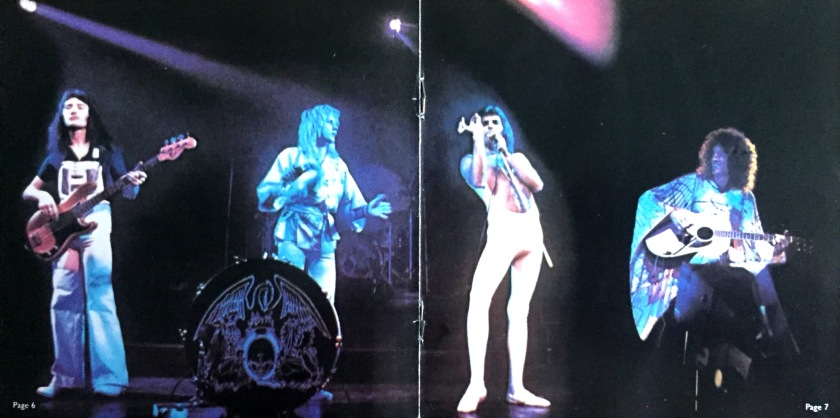 Centre spread from the booklet in A Day At The Races, showing a photo of Queen performing on stage. From left to right, John is playing bass guitar, Roger is standing by a small bass drum while playing a tambourine, Freddie is singing in his white low-cut jumpsuit, and Brian is sitting on a stool playing acoustic guitar.