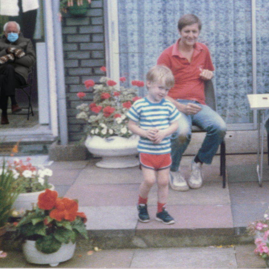 Glen, as a young child, is standing and smiling on a paved garden patio, wearing a blue and white striped t-shirt, red shorts and black trainers. His father, sat behind him in a red shirt, blue jeans and white trainers, watches with a smile. Flower pots nearby contain a mix of red and white flowers. Bernie Sanders in his coat and mittens from President Biden's inauguration, an image that went viral in January 2021, is sitting in the kitchen doorway in the background.