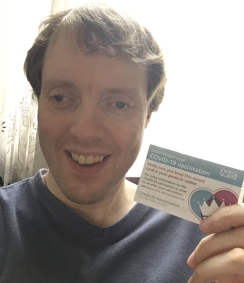 Glen smiling as he holds a small NHS card. The right side of the card shows a heart image, filled half with blue, half with red, and with a white crown on the top. Text on the left of the card reads Don't forget your Covid-19 vaccination. Make sure you keep this record card in your purse or wallet. For more information on the Covid-19 vaccination or what to do after your vaccination see www.nhs.uk/CovidVaccine. Covid-19 immunisation. Enjoy life, protect yourself.