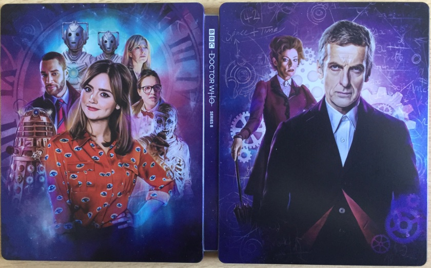 Steelbook cover for the Doctor Who Series 8 Blu-ray, showing Peter Capaldi's Doctor with Clara, Missy, the Cybermen and other characters from the series, against a dark blue background decorated with cogs, bubbles, and a large clock face.