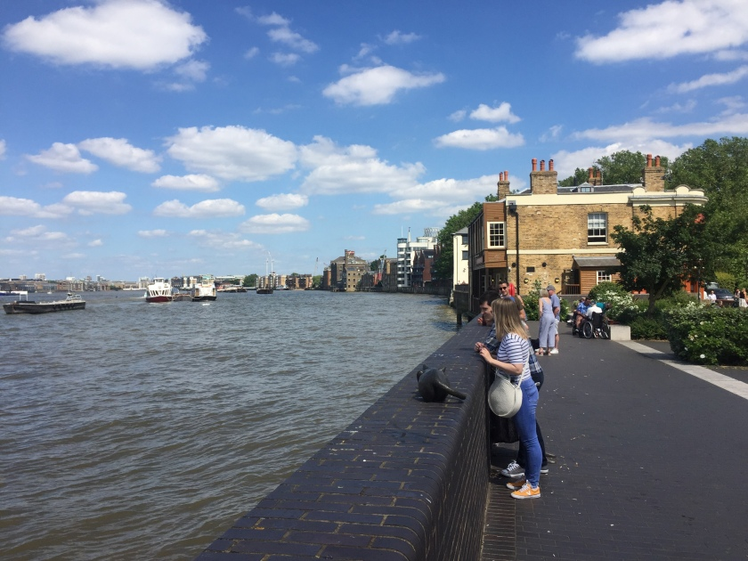 People standing by a wall and looking out over the River Thames