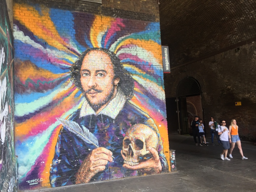 A large mural of William Shakespeare holding a quill in his right hand and a skull in his left, against a colourful swirling background.
