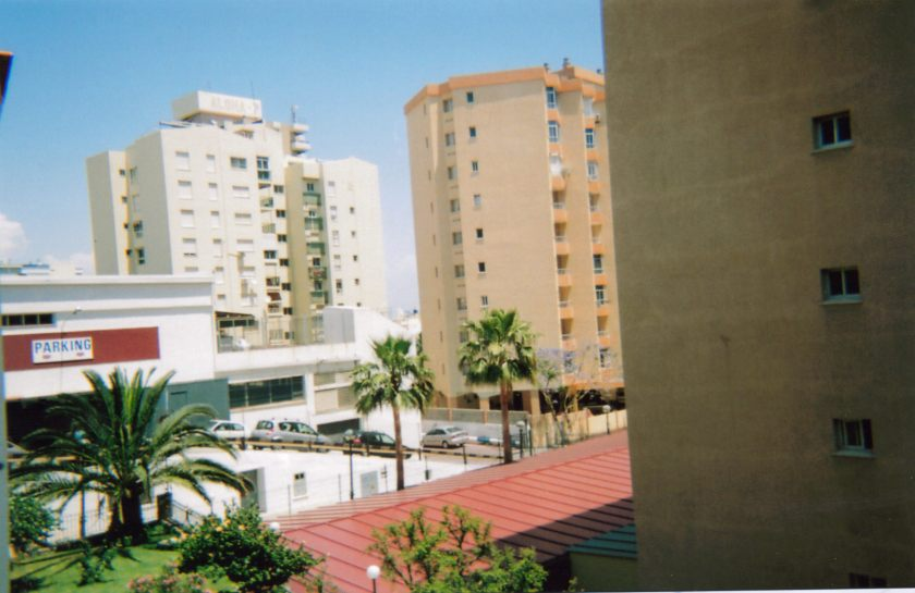 View from the balcony of our Spanish apartment, from which we can see palm trees, the roofs of nearby buildings, and a couple of taller apartment blocks behind them.