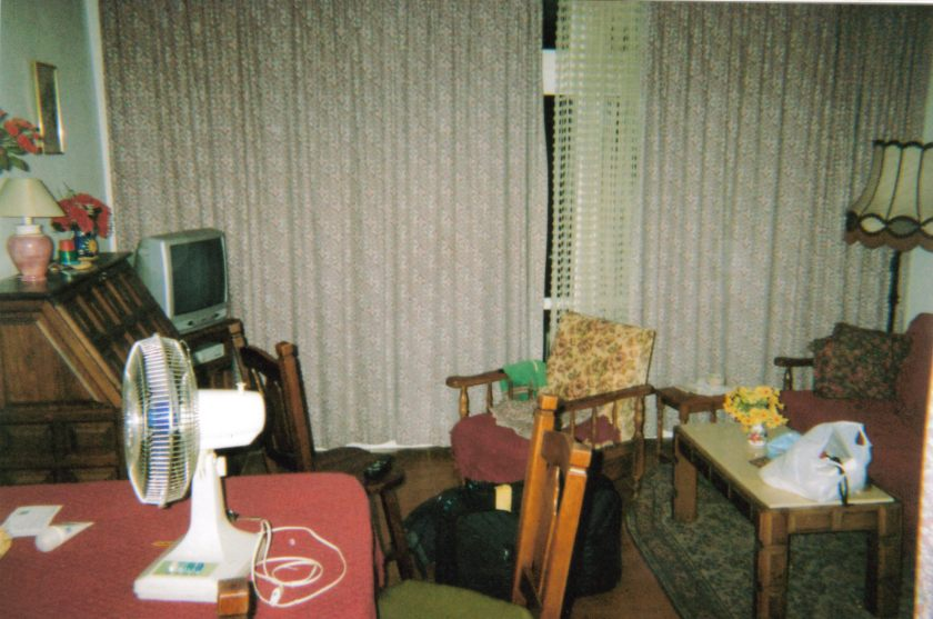 The lounge in my Spanish apartment, including tables and chairs, a portable electric fan, a TV in the corner, and curtains across the doors to the balcony.