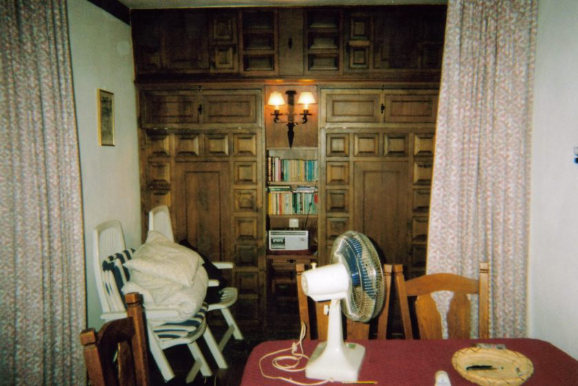 Another view of the lounge in my Spanish apartment, looking towards a wood panelled wall, which actually consists of a pull-down bed on either side of the lights, bookshelves and radio in the centre.