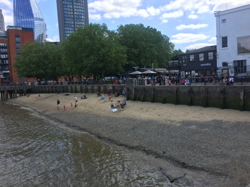 Adults and children on a small beach by the Thames, while lots of people walk along the main path behind them.