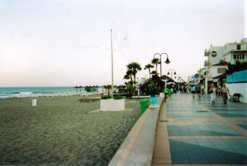 The beach at La Carihuela, people walking down a wide path next to it, and some palm trees visible in the distance.