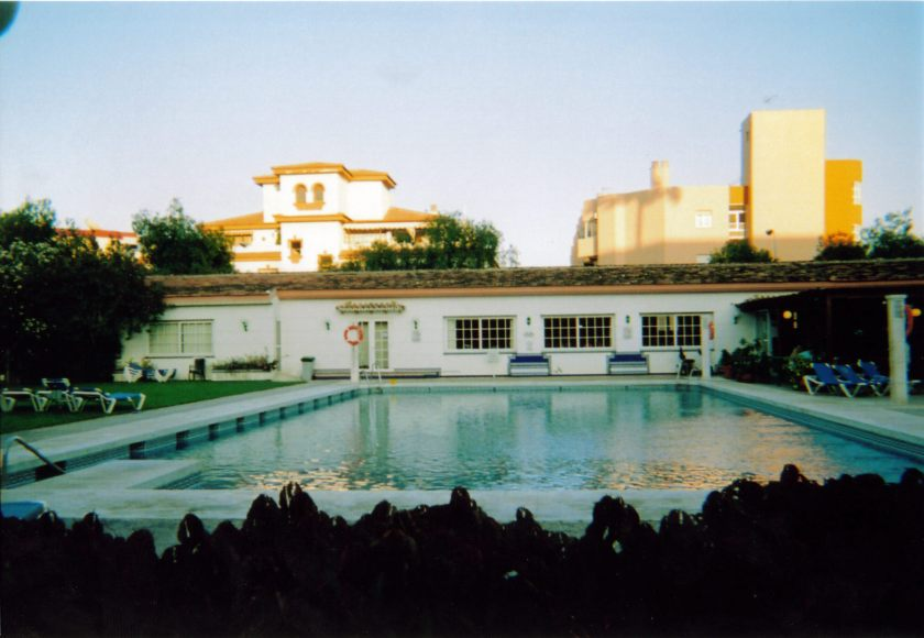 Swimming pool at Carihuela Park Palace, with a few sun loungers available nearby.