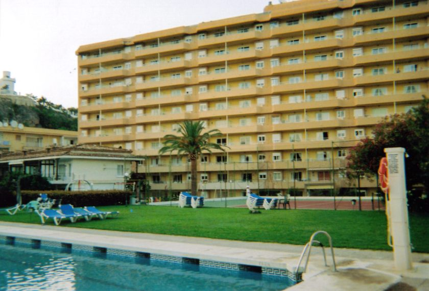An area of grass next to a swimming pool, with a palm tree and some sun loungers, in front of a tall apartment block, at Carihuela Park Palace.