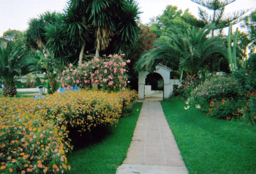 A path leading to a white archway, with greenery and colourful flowered bushes on each side, at Carihuela Park Palace.