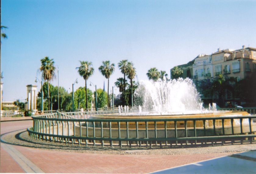 Large circular fountain in Malaga, with palm trees in the background.