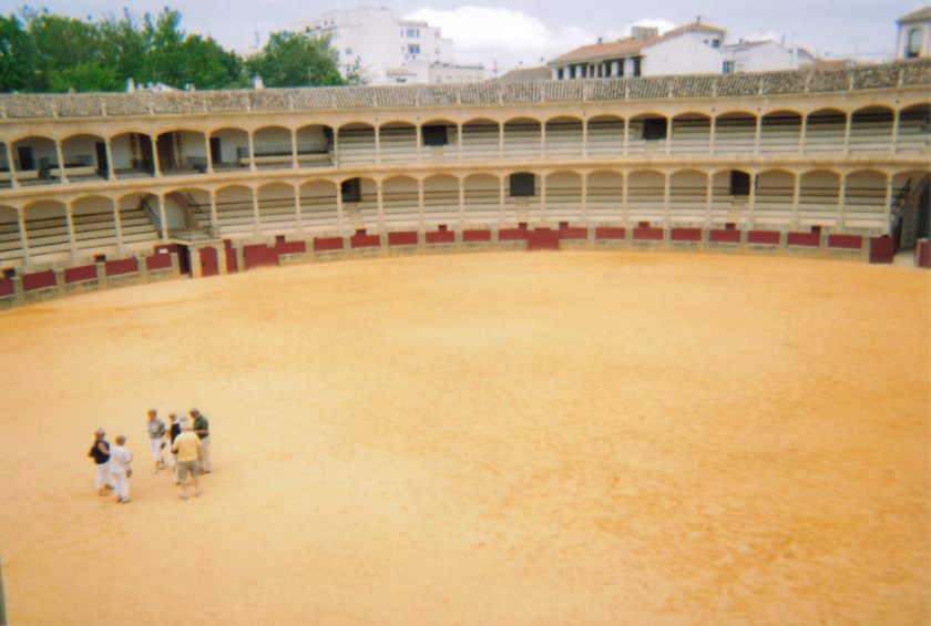 Large round bullring in Ronda, with arches in front of the 2 floors of seating all around the edge.