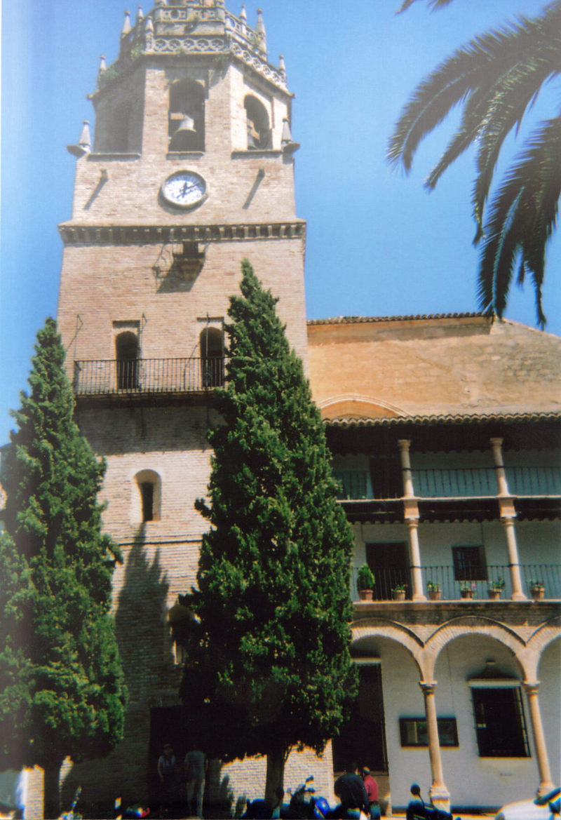 Church of Santa Maria La Mayor in Ronda. A tall bell tower, with a small clock just below the bell, is connected to a smaller three-storey structure with arches along the lower floor.